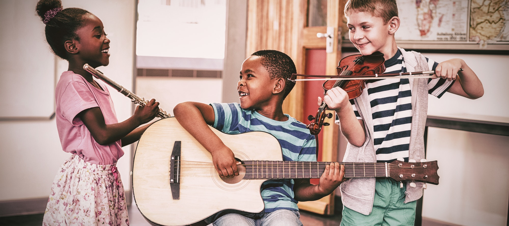 Children playing musical instruments in classroom