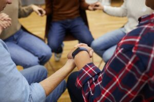 People Holding Hands in Support Group
