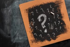 Sketched question marks on cardboard paper