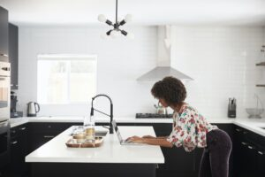 Woman At Home Standing At Kitchen Island Whilst Using Laptop